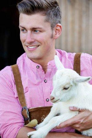 blond bavarian man holding a little white goat