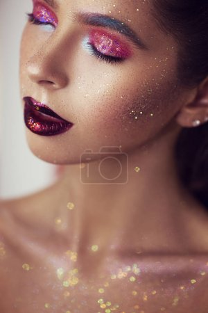Photo for Young beautiful girl in art makeup with shining, sequins on her face. perfect skin and lips. Concept of the magic effect on face - Royalty Free Image