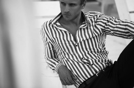 Photo pour Jeune beau modèle posant sur la plage chaise longue - image libre de droit