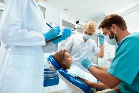 A dentist is preparing to treat the teeth of a little girl. There are nurses around. Girl smiling