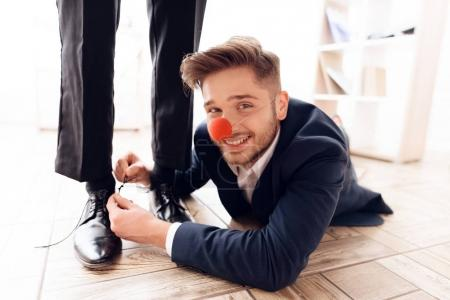 A man with a clown's nose under the table to tie laces to his business colleague.