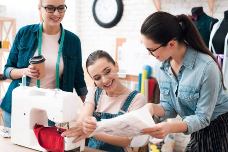 Photo pour Trois femmes à l'usine de confection. L'un d'eux montrant blueprint. Ils sont heureux. - image libre de droit