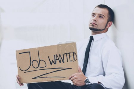 A young man is looking for a job. The guy looks at the job ads. Job wanted.