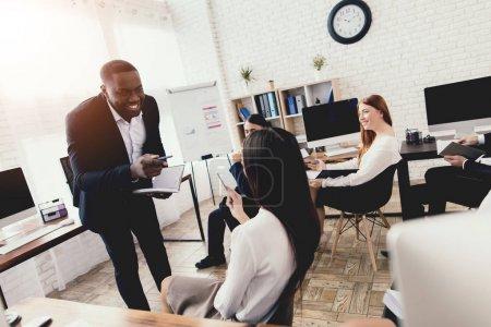 Photo pour Un homme noir parle aux employés d'un bureau d'affaires lors d'un séminaire. Il est de bonne humeur, il sourit du tout . - image libre de droit