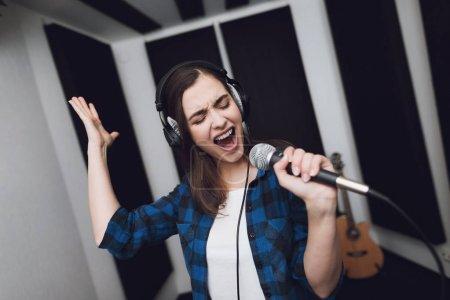 Photo pour La jeune fille chante sa chanson dans un studio d'enregistrement moderne. Elle chante la chanson très émotionnel. Devant elle est un microphone de studio. - image libre de droit