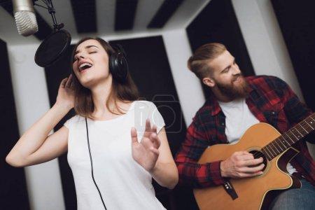 Photo pour Une fille et un gars chantent une chanson à une guitare dans un studio d'enregistrement moderne. La jeune fille chante, et le gars joue de la guitare. - image libre de droit