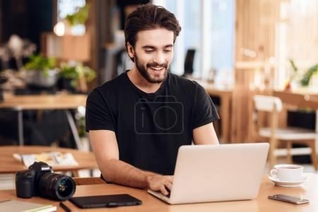 Photo for Freelancer bearded man in t-shirt typing at laptop sitting at desk. - Royalty Free Image