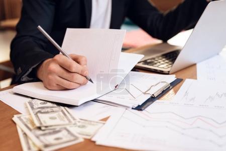 Freelancer man taking notes in notebook at laptop sitting at desk.