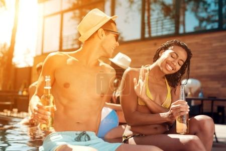 Young guy in summer straw hat flirts with girl in swimsuit that avoids him at swimmingpool.