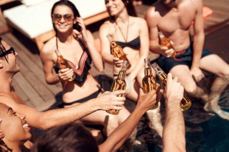 Photo pour Joyeux amis acclamant avec des bouteilles de bière dans la piscine. Parti de la piscine. Jeunes gens heureux s'amuser et profiter de summertime dans aquapark. - image libre de droit