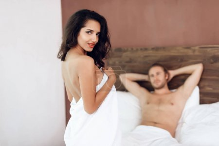 Beautiful passionate couple is having sex on bed. Romantic moments of young couple in bedroom. Intimate affinity. Sexual relations among young people.