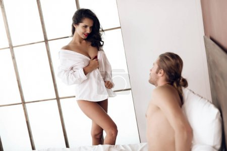 Passionate woman dressed in only man's shirt playfully looks at man lying in bed. Intimacy. Sexual relations. Intimate affinity.