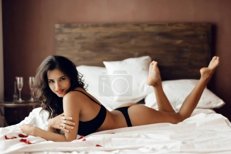 Sexual young brunette in black lingerie lays in erotic pose on white bed sheets in bedroom. Desire and temptation.