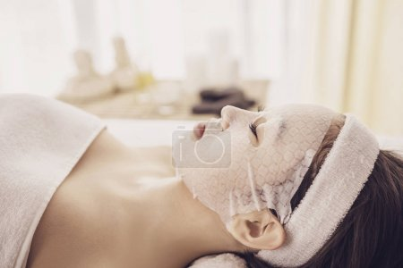 Spa therapy for young asian woman receiving facial mask at beauty salon