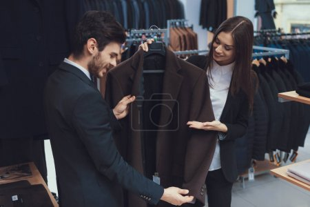 Photo for Beautiful elegant girl presents business style jacket to confident man in men clothing store. Boutique of business suits. - Royalty Free Image