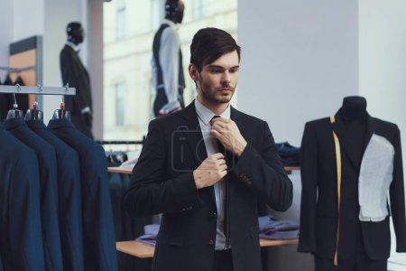 Photo for Successful young businessman measures jacket in business mens clothing store. Dressing room. Boutique of business suits. - Royalty Free Image