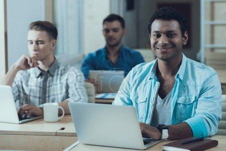 Photo pour Jeunes étudiants assis à un bureau interagissent avec l'ordinateur portable et tablette ordinateur et lectures de livres. Éducation. Université. - image libre de droit