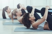 Beautiful women are engaged in pilates in gym.