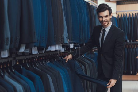 Confident young man looks at jackets for sale in showroom of men business clothing store.