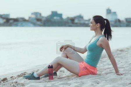 junge Sportlerin ruht sich nach Strandlauf aus.