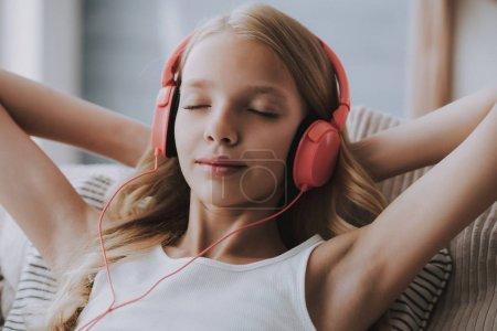 Teenage girl listens to music on headphones, closing eyes.