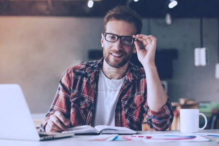 Photo for Handsome designer in casual clothes and eyeglasses is using laptop, making notes, looking at camera and smiling while working in his studio - Royalty Free Image