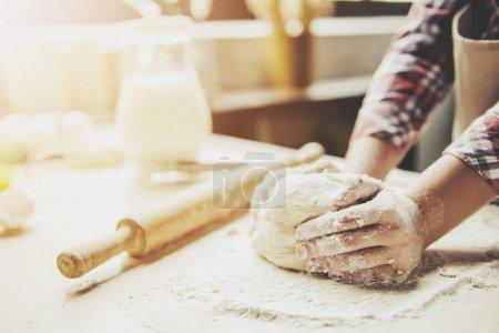 Photo pour Image recadrée de mignonne petite fille pétrissant la pâte pour la cuisson - image libre de droit