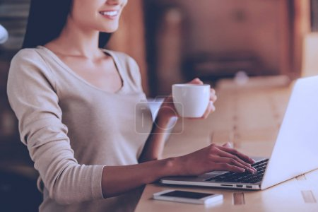 Photo for Cropped image of beautiful designer drinking coffee and smiling while working with a laptop in cafe - Royalty Free Image