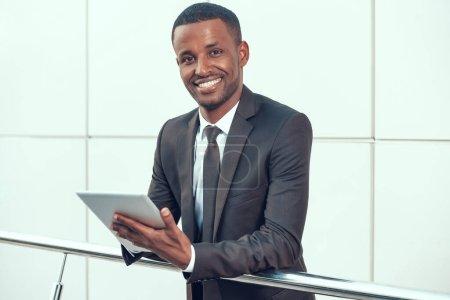 Photo pour African Businessman Working on Tablet. Beau entrepreneur debout et souriant. Directeur d'entreprise au lieu de travail. - image libre de droit