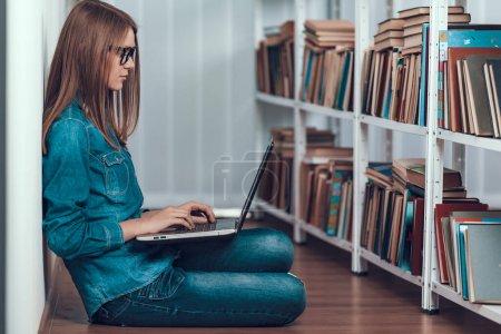 Photo pour Smart Girl dans les lunettes de vue lit sur ordinateur portable et fait de la recherche. Adolescent assis sur le sol de la bibliothèque. Étudier pour les examens . - image libre de droit