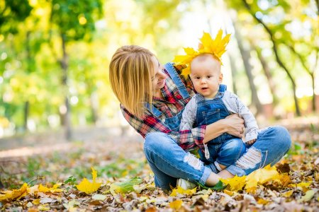 young mother playing with baby in the park in autumn