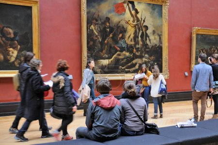 Tourists look at the paintings at the Louvre Museum