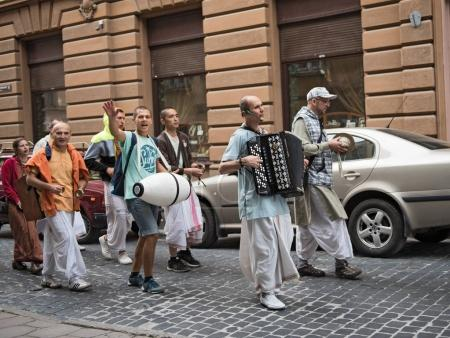 A group of hare Krishnas pulling singing through the old town of Lviv, Ukraine