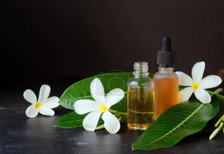 Photo pour Petit verre bocaux avec huile et fleur de frangipanier Plumeria fleurs de patchouli pour des soins spa sur un fond noir, mise au point sélective - image libre de droit