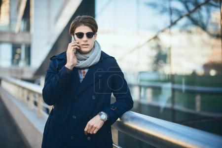 Photo for Young businessman using smart phone while standing on the street. - Royalty Free Image