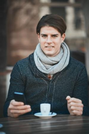 Portrait of young businessman using smart phone in coffee shop.