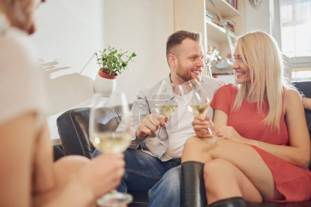 Photo for Friends cheering with wine at house party. - Royalty Free Image