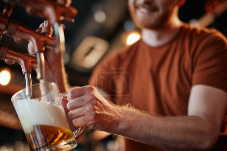 Photo for Close up of caucaisan ginger bartender pouting beer at pub. - Royalty Free Image