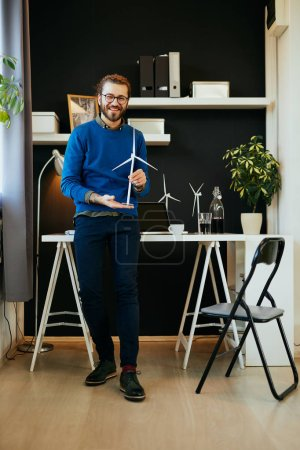 Foto de Jóvenes y simpáticos ingenieros caucásicos sonrientes en su oficina, mostrando el modelo de molino de viento y mirando la cámara.. - Imagen libre de derechos