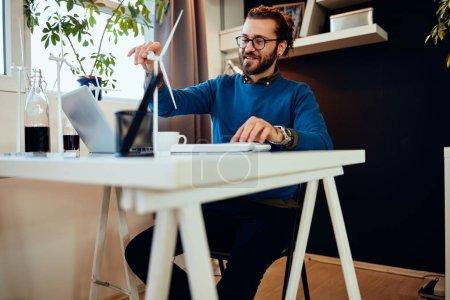Foto de Empresario caucásico cojinoso sentado en su oficina y que trabaja en un proyecto importante. Concepto sostenible. - Imagen libre de derechos