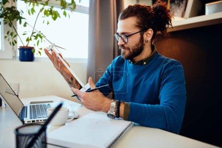 Foto de Joven ingeniero caucásico soportado sentado en su oficina, manteniendo el modelo de molino de viento y pensando en cómo rediseñarlo. Concepto sostenible. - Imagen libre de derechos