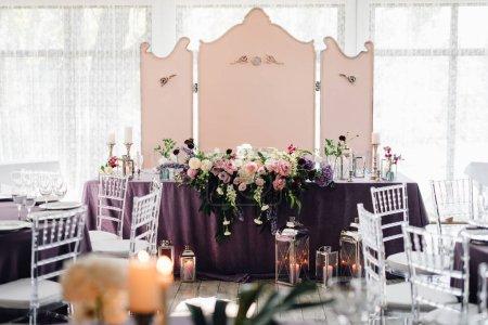 Photo pour Restaurant lumineux avec des tables recouvertes de tissu violet et des fleurs décorées de bougies, porcelaine et verres pour le dîner de mariage - image libre de droit
