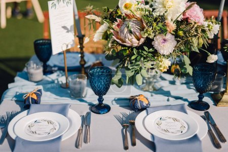 Dinner table with blue cloth, rich blue tableware, floral compositions and menu card