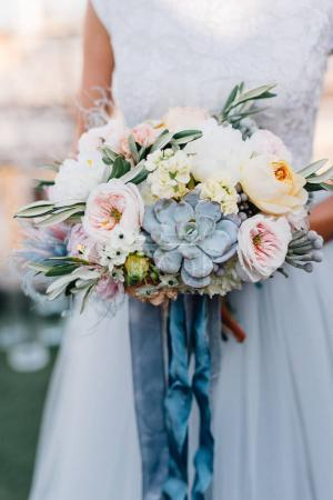 Bride in white wedding dress holds colorful wedding bouquet in her arms