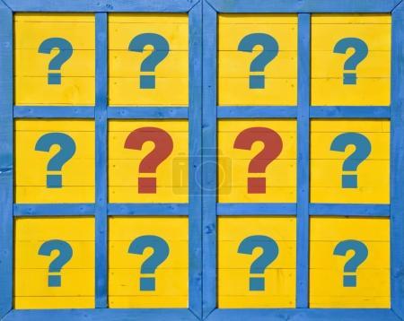 Photo pour Point d'interrogation rouge et bleu sur une fenêtre en bois fermée - image libre de droit