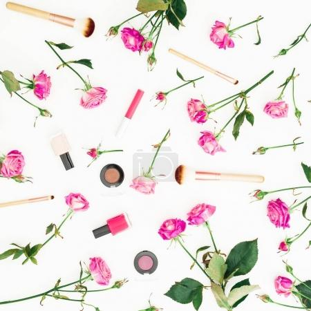 Pattern of pink rose flowers and cosmetics on white background. Flat lay, top view