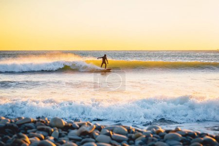 Photo for Surfer riding on perfect ocean wave at sunset. Winter surfing in swimsuit - Royalty Free Image