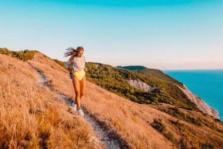 Photo pour Femme heureuse dans la nature au coucher du soleil chaud. Joyeuses vacances à la montagne - image libre de droit