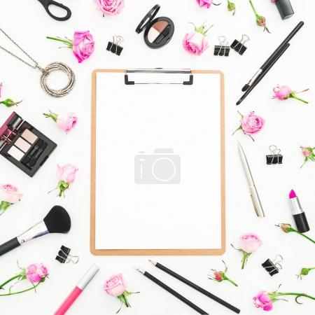 Woman workspace with cosmetics clipboard, accessories and pink roses on white background. Top view. Flat lay. Beauty blog background