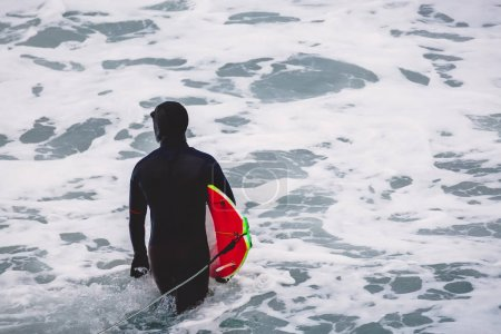 Surfer riding on perfect ocean wave at sunset. Winter surfing in swimsuit